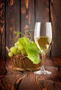 Glass of white wine and grapes Stock Photos