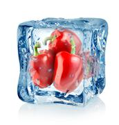 Ice cube and red peppers Stock Photos