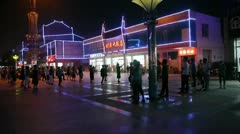 Dancing Chinese people crowd in the square at night.Flashing neon Commercial. Stock Footage