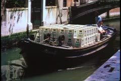 Barge moving through a narrow canal of Venice, Italy, loaded with crates Stock Footage