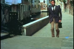 Italian Family, Venice, Italy, Father walks down calle to work with briefcase Stock Footage