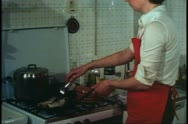 Woman, Venice, Italy, in her kitchen, wide shot fish frying Stock Footage
