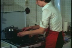 Woman, Venice, Italy, in her kitchen, putting fish into skillet Stock Footage