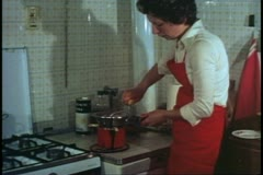 Woman, Venice, Italy, in kitchen, turning sieve handle to make pasta sauce Stock Footage