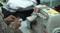 Textile Garment Factory Workers: Worker unwraps bundle at machine & barcode - stock footage