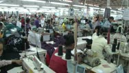 Stock Video Footage of Textile Garment Factory Workers: Move into table of workers folding fabric