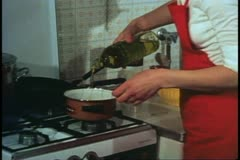 Woman, Venice, Italy, in her kitchen, putting oil into pot Stock Footage