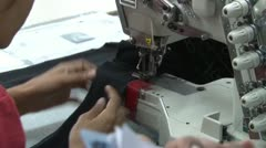Textile Garment Factory Workers: Telephoto Close Up of worker at sewing machine Stock Footage