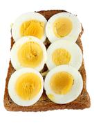 slices of hard boiled egg on toast. - stock photo