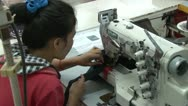 Textile Garment Factory Workers: OTS garment worker CU sewing machine #2 Stock Footage