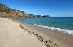Porthcurno sandy beach shore line and logan rock in cornwall uk. Stock Photos