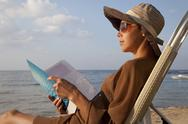 Woman reading book at beach Stock Photos