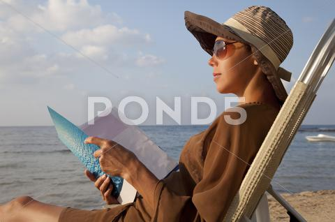 Stock photo of woman reading book at beach