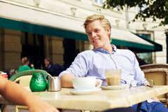Handsome guy hanging out in a street cafe Stock Photos