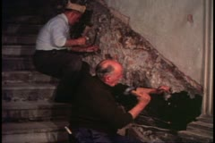 Scuola restoration, Venice, Italy, interior stairs, two workers chipping away Stock Footage