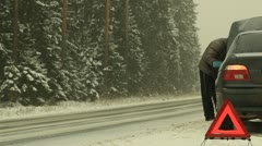 Man near broken car on the road in snow storm Stock Footage