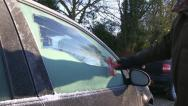 Scraping ice off a car window Stock Footage