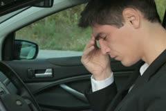 Sad businessman with headache sitting in the car  NTSC Stock Footage