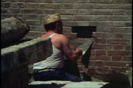 Stock Video Footage of Bricklayer inserting bricks in wall of Arsenal, Venice, Italy, medium close up