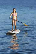 Mixed race girl paddle boarding Stock Photos