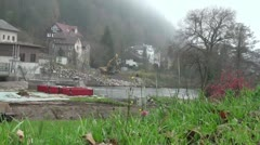 An excavator builds a rocky wall at the shore of river Stock Footage