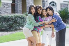 Hispanic family hugging - stock photo