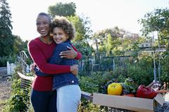 Mother and daughter gathering vegetables in community garden Stock Photos