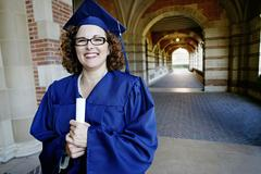 Smiling Caucasian woman holding graduation diploma Stock Photos