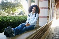 Mixed race college student sitting with feet up Stock Photos