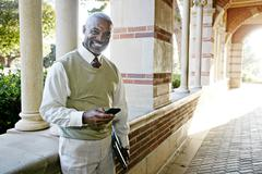 Black professor text messaging on cell phone Stock Photos