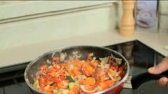 Tossing vegetables in a pan Stock Footage