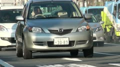 Rush hour traffic in Japan, cars drive through busy streets of Kyoto Stock Footage