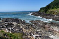 Waves rush ashore at devils punch bowl Stock Photos