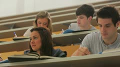 Woman sitting at the lecture hall with hand up Stock Footage