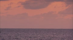 Boat in the Distance of Purple scene of ocean and skies Stock Footage