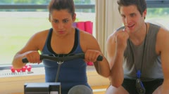 Woman at the rowing machine supporting by a coach Stock Footage