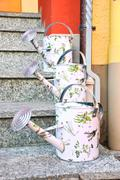 watering cans on the stairs - stock photo