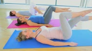 Women in yoga class doing legs exercises Stock Footage