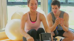 Happy woman at the rowing machine supporting by a coach - stock footage