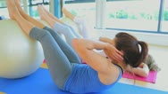 Concentrated women doing sit ups Stock Footage