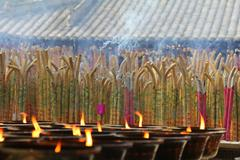 Incense burning in a temple, with candles. - stock photo