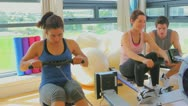 Women at the rowing machine supporting by a coach Stock Footage
