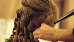 Hairdresser curls hair of model on fashion show Stock Footage