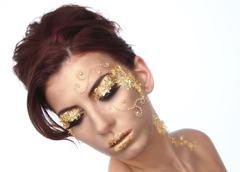 Beautiful woman adorned with gold leaf cosmetics Stock Photos