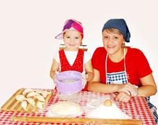 Mother and daughter make rolls with flour.JPG Stock Photos