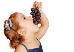 little girl eating grape.JPG - stock photo