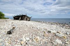 Old wooden shipwreck at coast Stock Photos