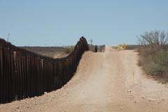 Fence and road at southern border of USA (HD)c Stock Photos