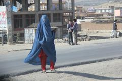 Muslim lady completely covered in hot sun crossing street in middle east (HD)c Stock Photos