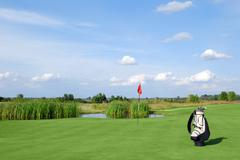 Golf field with red flag and bag.JPG Stock Photos